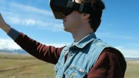 De mens in 360Vr-Helm bij de Meerbank gaat weg Jonge Mens in Park in Autumn Landscape Watching Video 360 Graden binnen stock video
