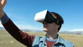 De mens in 360Vr-Helm bij de Meerbank gaat weg Jonge Mens in Park in Autumn Landscape Watching Video 360 Graden binnen stock videobeelden