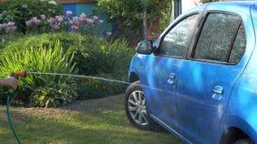 De mens wast de auto in de tuin stock footage