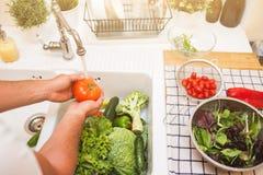 De mens wast groenten alvorens te eten Stock Foto's