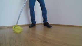 De mens wast de parketvloer met de gele zwabber stock videobeelden