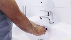 De mens wast zijn handen met water in de badkamers, de zorg en de lichaamshygiëne stock videobeelden