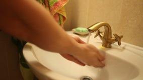 De mens wast zijn handen onder de kraan stock footage