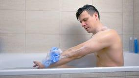 De mens wast zijn lichaamswashandje met de zitting van het douchegel in badkuip stock video