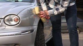 De mens wast zorgvuldig zijn favoriete auto met spons Autowasserettezelfbediening stock footage