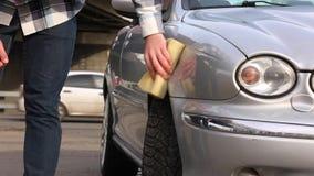 De mens wast zorgvuldig zijn favoriete auto met spons Autowasserettezelfbediening stock video