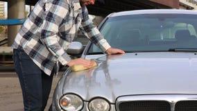 De mens wast zorgvuldig zijn favoriete auto met spons Autowasserettezelfbediening stock videobeelden