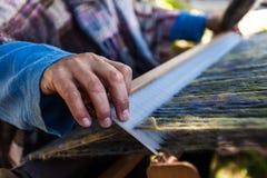 De mens weeft zeer buitensporige multi gekleurde wol gebruikend een houten weefgetouw - 4/6 stock foto