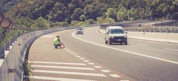 De mens in weerspiegelend vest schikt een gevarendriehoek, autoanalyse op de weg stock foto's