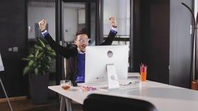 De mens wekte het springen van en het opheffen van handen op toen met succes het sluiten van grote overeenkomst stock footage