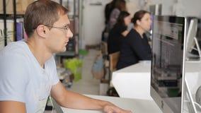 De mens werkt bij een computer in een lawaaierig en overvol bureau stock video