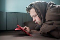 De mens werkt bij nacht, die aan de bank in de woonkamer met tablet liggen, die zijn hoofd behandelen met deken royalty-vrije stock foto