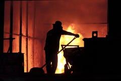 De mens werkt in het bespattende gesmolten ijzer - Voorraadbeeld stock afbeeldingen