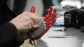 De mens werkt met hand bionische prothese, binnen zittend bij lijst stock videobeelden