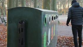 De mens werpt afval in een recyclingspost in een park stock videobeelden