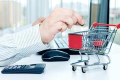 De mens werpt een muntstuk in spaarpot van de vorm van karretje Stock Foto