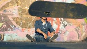 De mens werpt weg een skateboard in een park, langzame motie stock videobeelden