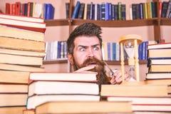 De mens, wetenschapper bekijkt zandloper De mens op ernstige en geschokte gezicht het letten op tijd gaat over, boekenrekken stock fotografie