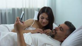 De mens wijdde zich aan mobiele spelen, die vrouw het flirten in bed negeren, verhoudingscrisis stock video