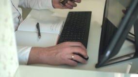 De mens in wit overhemd bij witte lijst gebruikt computer en telefoon stock video