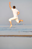 De mens in witte kleding springt Stock Foto's