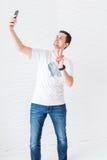 """De mens in witte T-shirt en jeans maakt selfie op een witte achtergrond en toont gebaar """"peaceÂ"""" Stock Foto"""