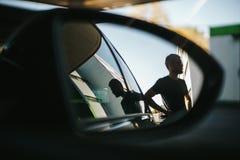De mens wordt gezien tijdens de zijaanzichtspiegel terwijl het van brandstof voorzien bij een benzinestation stock fotografie