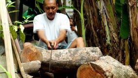 De mens zaagt een boomlogboek voor brandhout met een Japanse handzaag in binnenplaats stock videobeelden