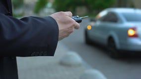 De mens zet autoalarm, veiligheidsconcept, risico om die aan auto te kapen op straat wordt geparkeerd stock footage
