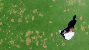 De mens zet bal in een gat terwijl het spelen van golf op een cursus stock video