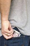 De mens zet contant geldbankbiljetten in achterzak van jeans Stock Afbeeldingen