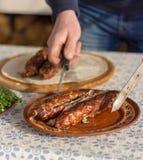 De mens zet een kebab op een plaat stock afbeeldingen