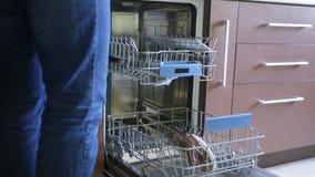 De mens zet een paar platen in een afwasmachine stock video