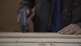 De mens zet het in de schede steken rond voorbereide houten raad door voornaamste kanon stock footage
