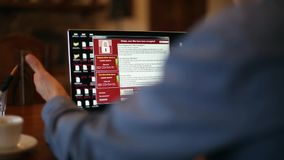 De mens zet laptop aan wacht op ladingscomputer en te weten komt het door een ransomware spyware virus wordt besmet dat is