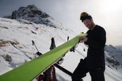 De mens zet op zijn skihuid Stock Foto