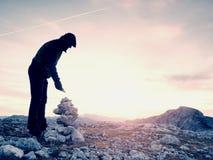 De mens zette de laatste steen intopeak van piramide Evenwichtige steenpiramide op bergtop Stock Fotografie
