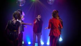 De mens zingt in een retro microfoon rond mensen die dansen te zingen Rook achtergrond stock video