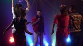 De mens zingt in het retro microfoonmensen dansen Rook achtergrond Langzame Motie stock video