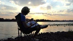De mens zit als Voorzitter op Riverbank, leest, en Dranken bij Zonsondergang in langzame mo stock videobeelden