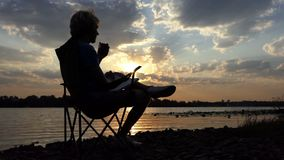 De mens zit als Voorzitter op Riverbank, leest, en Dranken bij Zonsondergang in slo-Mo stock video