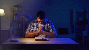 De mens zit bij een lijst en leest een gebed stock videobeelden