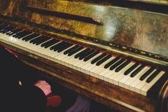 De mens zit bij een oude uitstekende piano stock fotografie