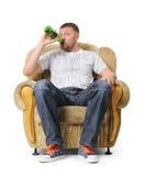 De mens zit in een leunstoel en drinkt bier Stock Foto's