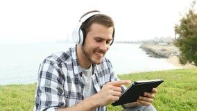 De mens zit en luistert en let op media op tablet stock video