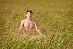 De mens zit in gras in lotusbloem stelt Stock Afbeeldingen