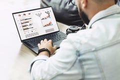 De mens zit in koffie, werkt aan laptop met grafieken, grafieken op het scherm De zakenman plant zaken Online op de markt brengen royalty-vrije stock afbeeldingen