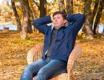 De mens zit ontspannen hebben als rieten voorzitter Stock Foto