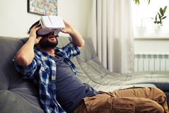 De mens zit op bank en het hebben van pret gebruikend witte VR-hoofdtelefoon Stock Foto