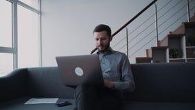 De mens zit op bank en werkt gebruikend draadloze laptop stock videobeelden